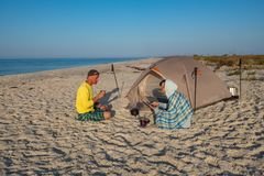 Travelers are relaxing next to tent on the beach drinking coffee. Using tablet pc and having fun. Happy people in nature Stock Photos
