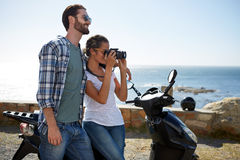 Travelers on a scooter, near the ocean, taking pictures Royalty Free Stock Image
