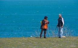 Travelers on the seashore, conversation Stock Photo