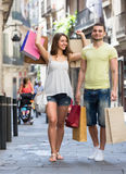 Travelers with shopping bags. Two travelers with shopping bags at city street Royalty Free Stock Photo