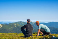 Travelers are sitting on the alpine meadow with map Royalty Free Stock Photos