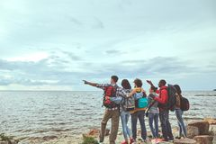 Travelers standing at the seashore looking for the ship stock photography