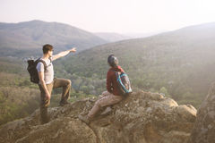Travelers staring at the mountains. Young couple staring at the mountains. Toned Image Royalty Free Stock Images