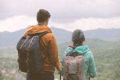 Travelers staring at the mountains. Young couple staring at the mountains. Toned Image Royalty Free Stock Photo