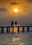 Travelers at sunset. Silhouette of two people at sunset on vacation, carrying their luggage Stock Photos