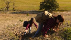 Travelers teamwork. tourist with backpacks help climb each other up the hill. backpackers help climb each other up the