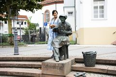 Travelers thai woman travel and posing with art old human statue. In lege cap ferret platz public park at Sandhausen village on August 25, 2017 in Heidelberg royalty free stock images