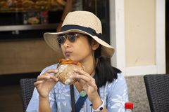 Travelers thai woman travel visit and sitting eat sandwiches with soft drinks at local restaurant. Travelers thai woman travel visit and sitting eat sandwiches stock images