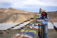 Free Travelers Thai Woman Travel Visit Stand For Take Photo With Prayer Flag For Blessing At Viewpoint With Mountains And Pangong Lake Royalty Free Stock Photo - 164339045