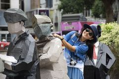 Travelers thai woman visit and posing with human statue at outdoor of Hong Kong Space Museum. Travelers thai woman visit and posing with human statue in garden stock images