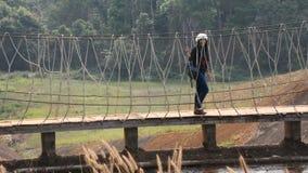 Travelers thai women visit walking on wooden suspension bridge in Pang Oung