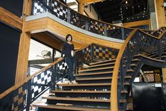 Travelers thai women walking up on classic wooden stairs in modern and luxury restaurant. Travelers thai woman walking up on classic wooden stairs in modern and royalty free stock photo