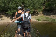 Travelers travel on the suspension bridge go trekking together. Active hikers. Trekking together. Eco tourism and healthy lifestyl. E concept. Two young Tourists Royalty Free Stock Photos