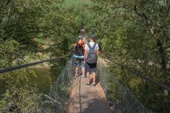 Travelers travel on the suspension bridge go trekking together. Active hikers. Trekking together. Eco tourism and healthy lifestyl. E concept. Two young Tourists stock photos