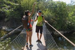 Travelers travel on the suspension bridge go trekking together. Active hikers. Trekking together. Eco tourism and healthy lifestyl. E concept. Two young Tourists Royalty Free Stock Photo