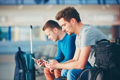 Travelers waiting for departure. Two friends traveling together. Travelers with mobile phones waiting at the airport departure area for their delay flight Stock Images