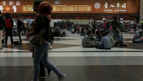 Travelers waiting and walking in ticket lobby at Taipei Train Station, slow motion stock video