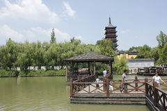 Travelers walking cross the wooden  bridge besides Haogu Tower (Jiaxing,China) Royalty Free Stock Photo