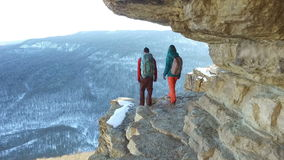 Travelers walking on edge of cliff. Couple of travelers walking on edge of cliff stock video