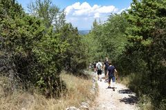 Travelers walking on tree trail in the National Park of Croatia in summer royalty free stock image
