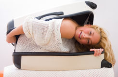 Traveling. A young woman getting out from a suitcase = part of a series Stock Photos