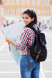 Traveling abroad. Beautiful girl with map smiling in the city Stock Image
