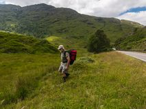 Traveling of active senior man. View of Scotland. Active senior man with red rucksack  taking care of his health condition Royalty Free Stock Image