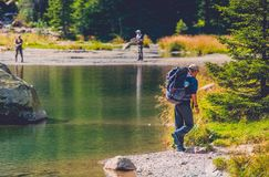 Traveling Adventurous Men. On the Edge of Scenic Mountain Lake. Caucasian Traveler with Large Backpack on the Mountain Trail Stock Photos