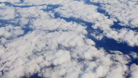 Traveling by air above clouds. View through an airplane window. Flying over the Mediterranean. Sea through cirrus and cumulus clouds and little turbulence stock video footage