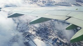Traveling by air above winter surface. View through an airplane window. Flying over the Moscow through clouds and little stock video