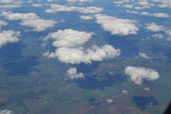 Traveling by air. View through an airplane window. Cirrus and cumulus clouds and little turbulence, showing Earth`s Stock Photo