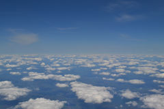 Traveling by air. View through an airplane window. Cirrus and cumulus clouds and little turbulence, showing Earth`s Royalty Free Stock Images