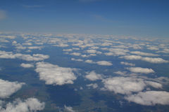 Traveling by air. View through an airplane window. Cirrus and cumulus clouds and little turbulence, showing Earth`s Stock Image