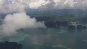 Traveling by air. View through an airplane window with cloud and hill island. Over Phuket Thailand stock video