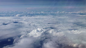 Traveling by air. View through an airplane window. Flying over the Mediterranean Sea through cirrus and cumulus clouds and little turbulence, showing Earths stock video