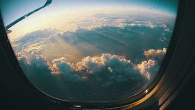 Traveling by Air. View through Airplane Window on Sun Background. View from an airplane window above the clouds on Sun Background. Traveling by air. View through stock video footage