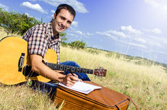 Traveling artist writes a song in nature Royalty Free Stock Photography