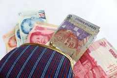 Traveling in asia concept. Mess with changing money - A concept photograph showing a female cloth canvas purse with assorted currency bank notes from different stock photography