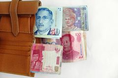 Traveling in asia concept. A concept photograph showing a brown leather wallet with different assorted currency bank notes from various asia countries, including royalty free stock image