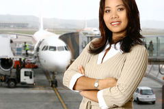 Traveling Asian businesswoman. Asian businesswoman in the departure hall about to go on her business trip, passenger boarding  plane in the background Stock Photos