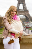 Traveling with baby. Beautiful young mother with her baby daughter in sling in Paris Royalty Free Stock Photo