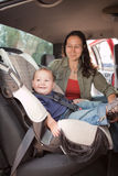 Traveling with a baby. Mother & baby in the back seat of a car on a road trip royalty free stock photography