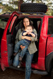 Traveling with a baby. Mother stepping out of the back seat of a car with a baby. Shallow DOF, boy's face in focus Stock Image
