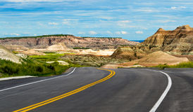 Traveling Through the Badlands of North Dakota. Traveling down a single  road inside the national park shows the striation of the rock formations and the vast Royalty Free Stock Photo