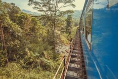 Traveling by blue train on bridge of green forests. Landscape of Sri Lanka. Stock Photo