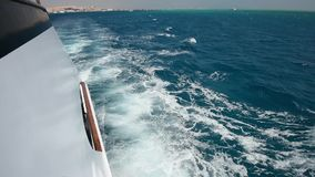 Traveling on board a luxury motor yacht across tropical ocean. View from side of a large luxury motor boat while sailing across tropical ocean landscape stock video footage