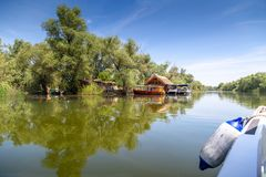 Traveling by boat through the Danube Delta. Landscape of the Danube Delta with reed huts and boats pontoons stock images