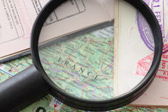 Traveling Bug. A magnifying glass focusing on the map of France with two open passports, suitable for traveling or holiday theme Stock Photos