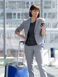 Traveling business woman looking at mobile phone Royalty Free Stock Photos