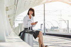 Traveling business woman with smart phone and luggage Royalty Free Stock Images